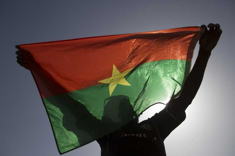 A pro-democracy protesters holds up a Burkina Faso flag at Place de la Nation in Ouagadougou