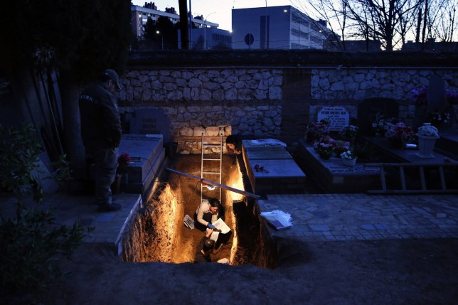 Members of the Association for the Recovery of Historical Memory (ARMH) take part in the exhumation of the grave in Guadalajara's cemetery, Spain, January 24, 2016. At the request of an Argentine judge in a lawsuit seeking redress for crimes committed during the 1936-39 civil war and the four-decade dictatorship of General Francisco Franco that followed, a Guadalajara court has authorised the exhumation of the grave, containing 22 bodies of people believed to have been killed by Franco's forces in the months after the end of the civil war. Picture taken January 24, 2016. REUTERS/Juan Medina      TPX IMAGES OF THE DAY