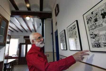 Un vecino de El Cabanyal muestra los cómics expuestos en su casa para la edición de este año de Portes Obertes./ Mónica Torres (El País)