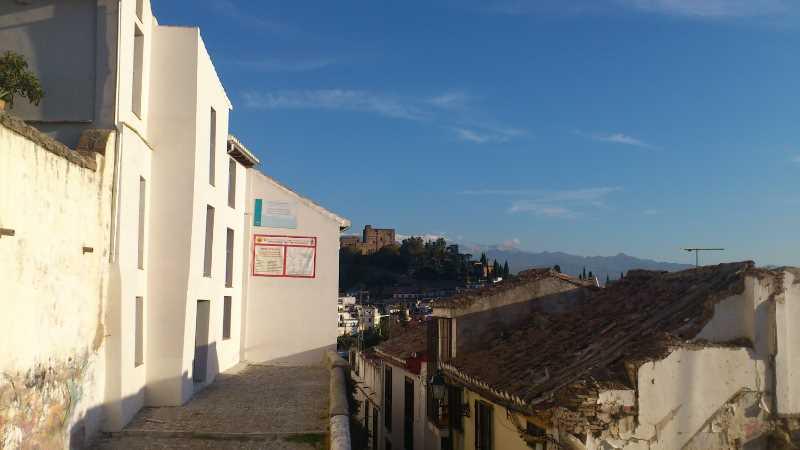 Vista de una calle del Albaicin con un edificio rehabilitado