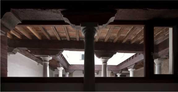 Vista de los capiteles y zapatas del patio desde la crujía de fondo,  dormitorio en planta baja de la única vivienda en dúplex. Fernando Alda es el autor de esta fotografía.