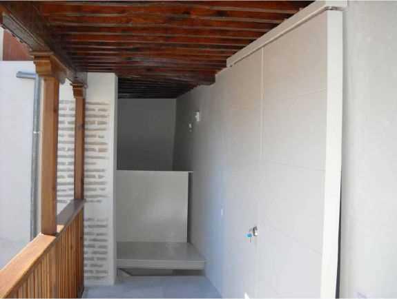Galería de la planta segunda: Puertas de vivienda cerradas sobre el hueco morisco original y al fondo detalle del desembarco de escalera de chapa de acero