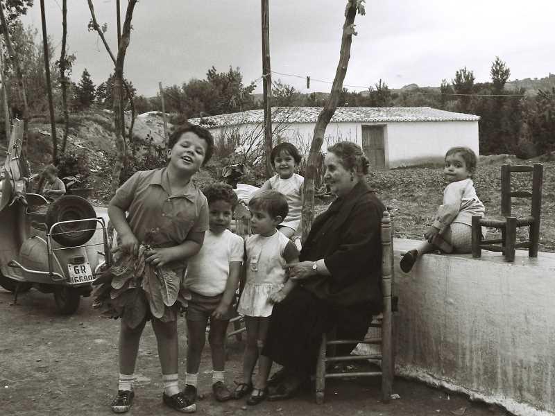 """Carmen Arenas Briñas con sus nietos y nietas, 1966: Fue maestra, se quedó viuda en la guerra y crió a tres hijas y dos hijos. En la fotografía está con algunos de sus veinte nietos y nietas.  Antiguamente se decía """"Mi mujer ha mal parío, trabajo perdío"""". Fuente: Torcuato Fandila"""