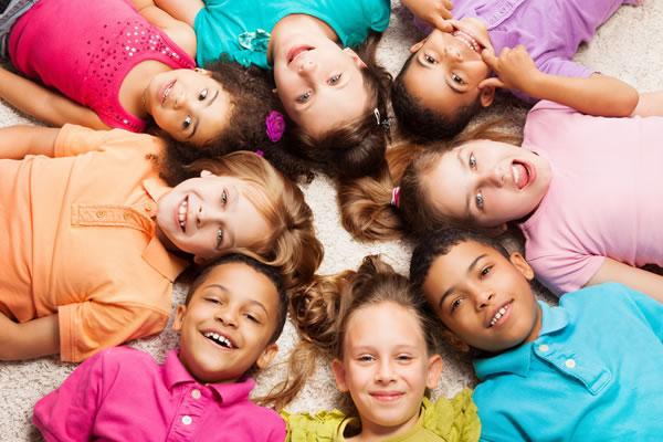 Un grupo de ocho niños sonríen formando una estrella en el suelo. :: FOTOLIA