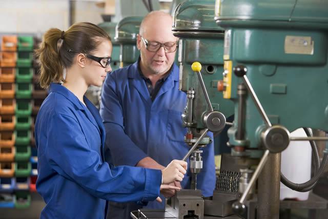 Un operario enseña a una compañera joven a utilizar una maquinaria. :: AGENCIAS